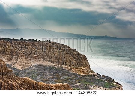 Torrey Pines cliff in pacific ocean in San Diego California cloudy with sun rays and haze