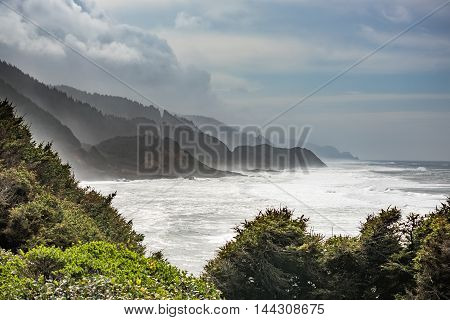 Stormy coastline in Oregon with fog and white ocean beach with cliffs and forests