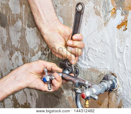Close-up of adjustable spanner in the hands of plumbing nut unscrews wall mount kitchen faucet water supply with two handles.