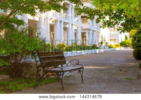 Street forged bench is in green Park on territory of departmental sanatorium Raduga. On background is white building of hospital with concrete columns.