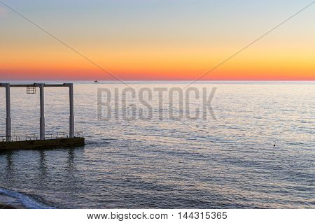 Concrete pier with a transport rail at top on seafront sinking into waves. Sunset on beach on Black sea in October. Sochi Krasnodarskiy kray Russia