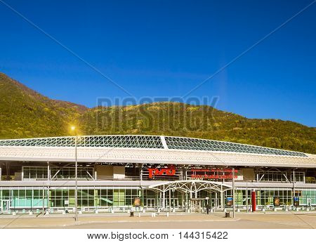 SOCHI RUSSIA - OCTOBER 31 2015: Railway Esto-Sadok station on the backdrop of the Caucasus mountains and blue sky. Logo of Russian Railways on facade. Krasnaya Polyana Sochi Krasnodarskiy kray Russia