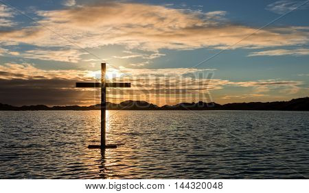 Black cross of salvation on a lake of water at sunset. And a spirit image of Jesus.