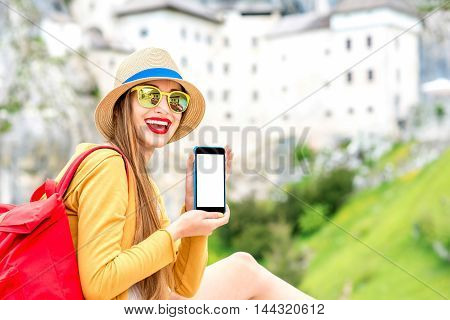 Young female traveler showing phone with empty screen near Predjama castle in Slovenia