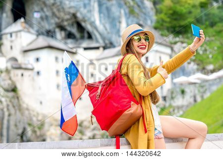 Young female traveler making selfie portrait near Predjama castle. This castle is a famous tourist attraction and a travel destination in Slovenia