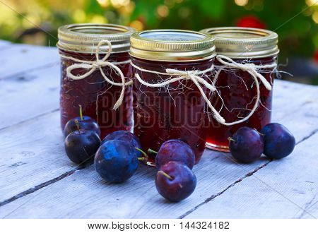 Bottles of homemade plum jam and some plums on an outside picnic table.
