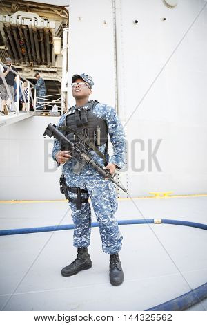 NEW YORK MAY 26 2016: Armed US Navy security personnel stand ready at the USS Bataan (LDH 5) an amphibious assault ship moored at Pier 88 for Fleet Week NY 2016.