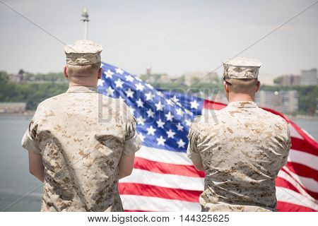 NEW YORK MAY 26 2016: Two US Marines stand near the American Flag that flies off the stern of the USS Bataan (LDH 5) an amphibious assault ship moored at Pier 88 for Fleet Week NY 2016.