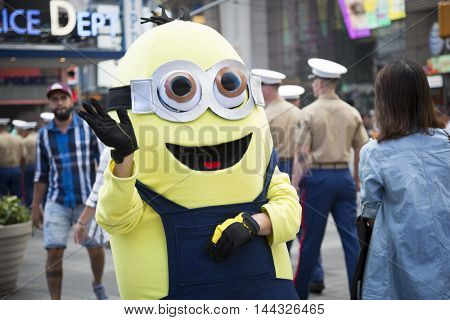 NEW YORK MAY 26 2016: Members of the U.S. Marine Corps walk past a minion character at the Armed Forces Recruiting Station on Military Island Pedestrian Plaza in Times Square during Fleet Week NY.
