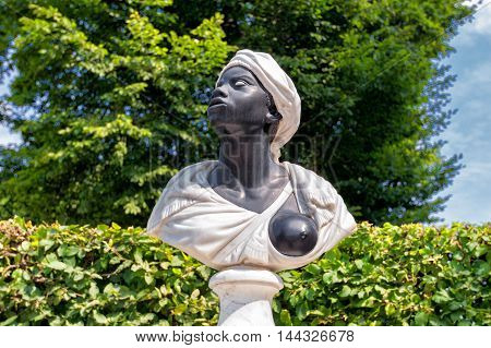 Black slave sculpture showing a breast in a public park at Potsdam poster