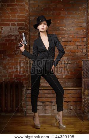 Noir Film Style Woman In A Black Suit With Gun