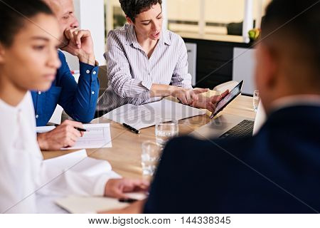 business meeting taking place in modern board room with four members attending and a mature caucasian busienss woman busy showing one of her colleagues charts on her electronic tablet.