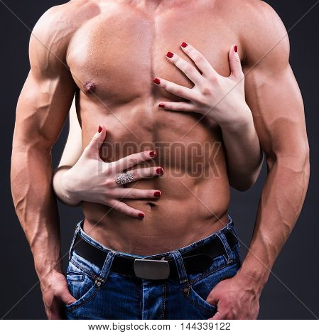 Love Concept - Close Up Of Female Hands Embracing Muscular Man Over Grey