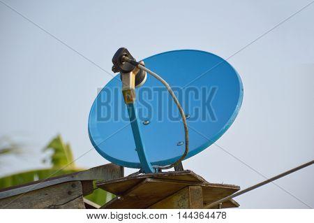 close up blue satellite dish on roof