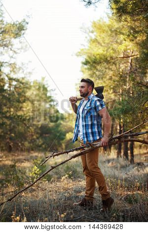 Lumberjack with an ax and firewood in the forest. Woodcutter in plaid shirt chopped wood for the fire. Felling trees. Logging. Manual labor.