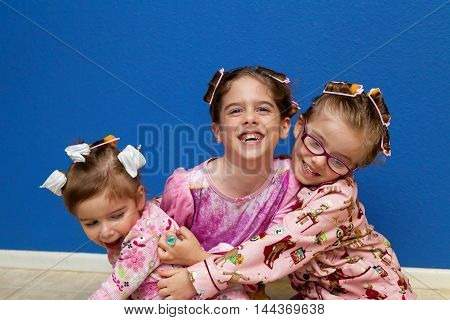 Three sisters sit on a linoleum floor wearing pajamas and curlers. They have on pink pajamas and are hugging each other.