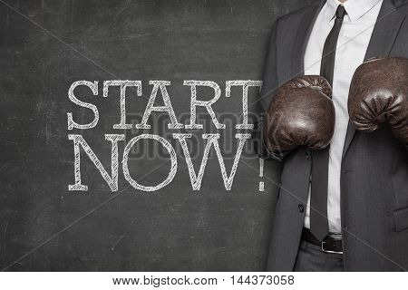 Start now on blackboard with businessman wearing boxing gloves