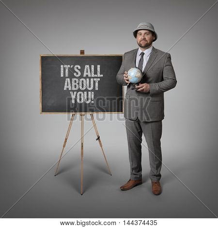 Its all about you text on blackboard with businessman holding globe in hands