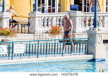BUDAPEST, HUNGARY - AUG 18, 2014: Unidentified man  walks near a pool of the Szechenyi Medicinal Bath complex , the largest medicinal bath in Europe, built in 1913
