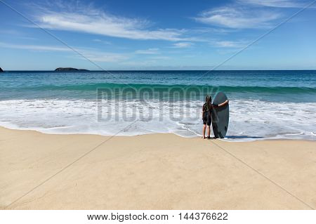 A young girl stands at the edge of the water with her surfboard at Zenith Beach - Nelsons Bay NSW Australia