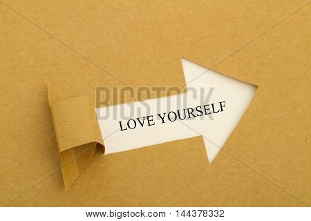 Love yourself message written under torn paper.