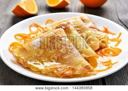 Delicious crepes suzette with orange syrup on plate