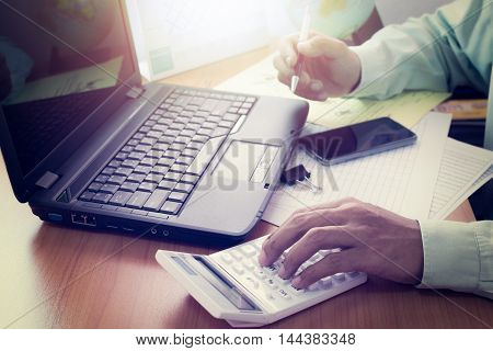 Hands of a man working with laptop calculator and holding a pen on office desk in shinning light