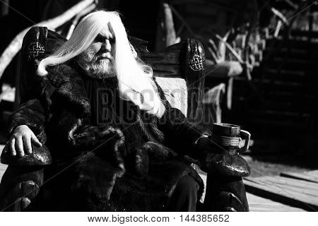 Druid old man with long silver hair beard in fur coat sits in chair with wooden mug black and white on grey background