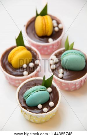 A mini cup cakes decorated macaroon on top