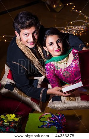 Indian young and handsome husband gifting necklace to his beautiful wife on the occasion of diwali or dipawali festival, happiness concept, selective focus