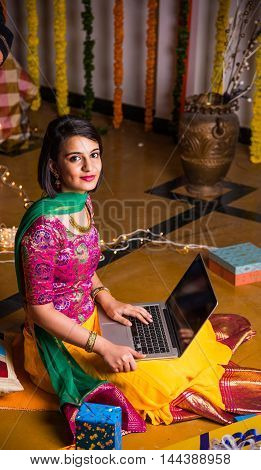 Indian young and beautiful female in traditional cloths using laptop on diwali festival