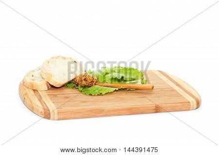 Two slice of bread and spoon with mustard lying on cutting board isolated over white background