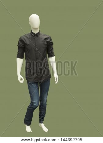 Full length male mannequin dressed in shirt and blue jeans isolated on green background. No brand names or copyright objects.