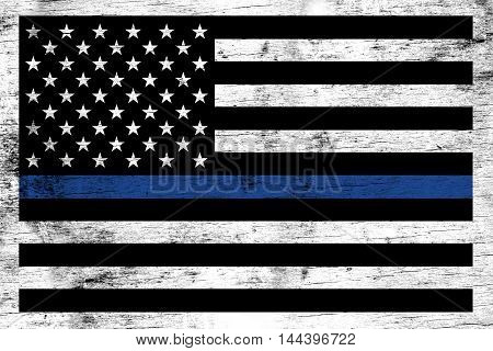 A police and law enforcement support flag stained over a weathered white wooden background.