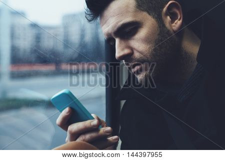 Young man using a smart phone in the streetcar