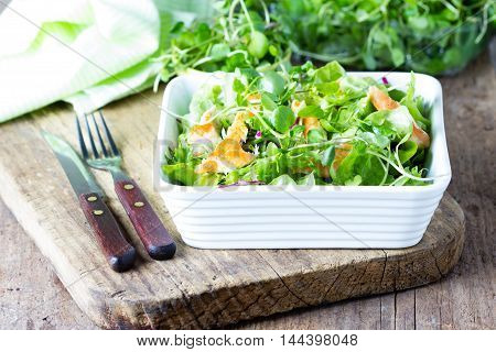 Fresh healthy vegetables lettuce and chicken salad in white bowl on wooden rustic cutting table on wooden old background. Caesar cesar salad.