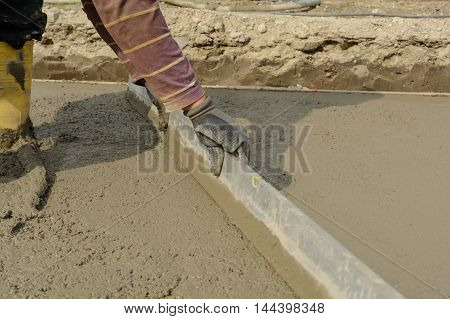 Mason pulls Screeding during concreting fresh concrete mix - closeup