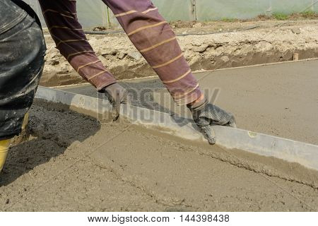 bricklayer pulls with a long spirit level concrete - closeup