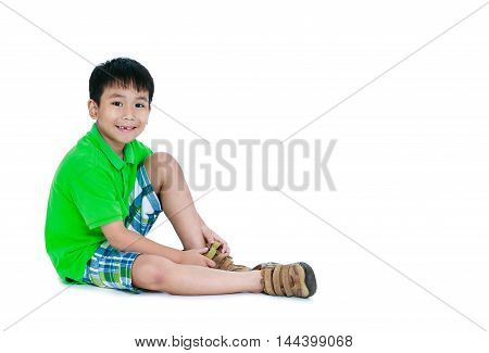 Full body of cute asian child smiling and put leather shoes on. Happy boy sitting on floor. Isolated on white background and free form copy space. Studio shot. Positive human emotion.
