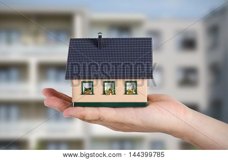 Replace flat to your own house. Hand holding miniature block of flats in background