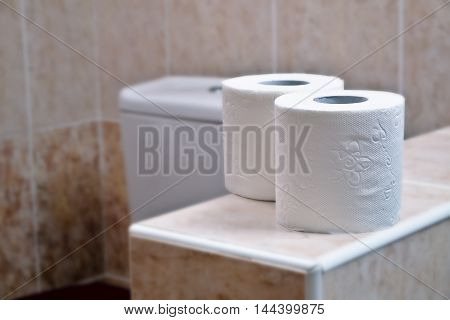 Two rolls of white toilet paper in the background