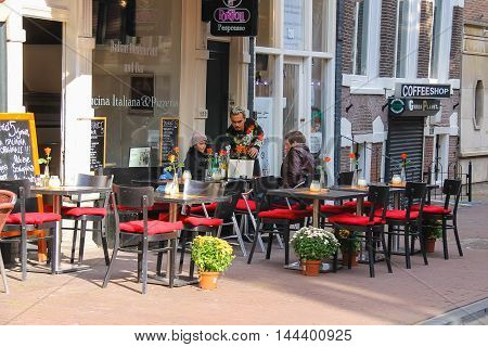 Amsterdam the Netherlands -October 03 2015: People resting in outdoor cafe in historic city centre