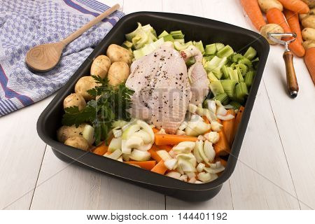 raw chicken with carrots potatoes celery onion parsley and garlic in a roasting tray