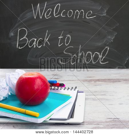 Apple with school supplies on white aged wooden table, blackboard and welcome back to school in background