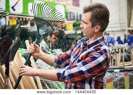 Man Chooses Rake Leaves In Store For Garden