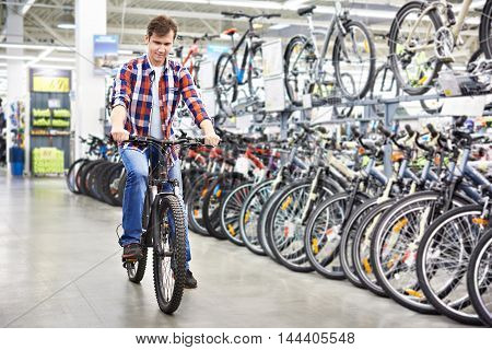 Man Checks Bike Before Buying In Shop