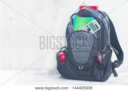 School backpack full of supplies on white desktop