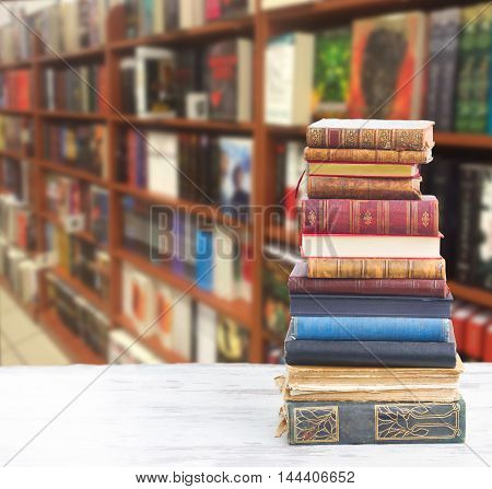 tower of books on white wooden desktop in bookstore