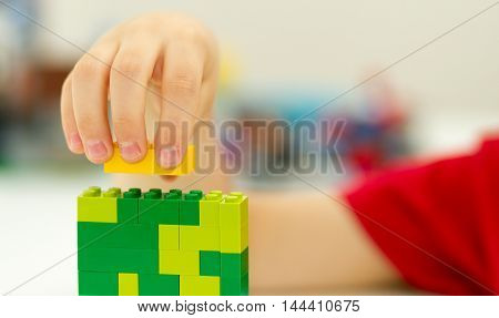 Orvieto, Italy - June 08th 2015: Hand ofChild playing with lego bricks . Lego is a popular line of construction toys manufactured by the Lego Group