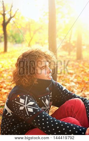 Young man sitting on autumn leaves in a sunset park, backlight outdoor, smiling and happy, long curly hairstyle